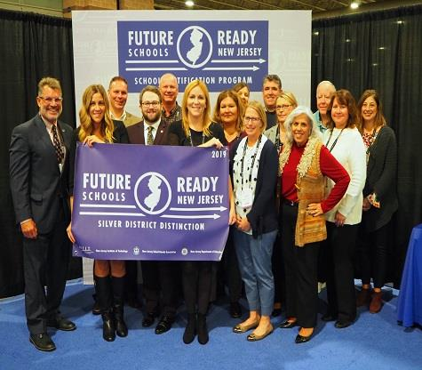 The MTPS Administrative Team and Board Members hold up a Future Ready Silver District Distinction banner at NJSBA Workshop.